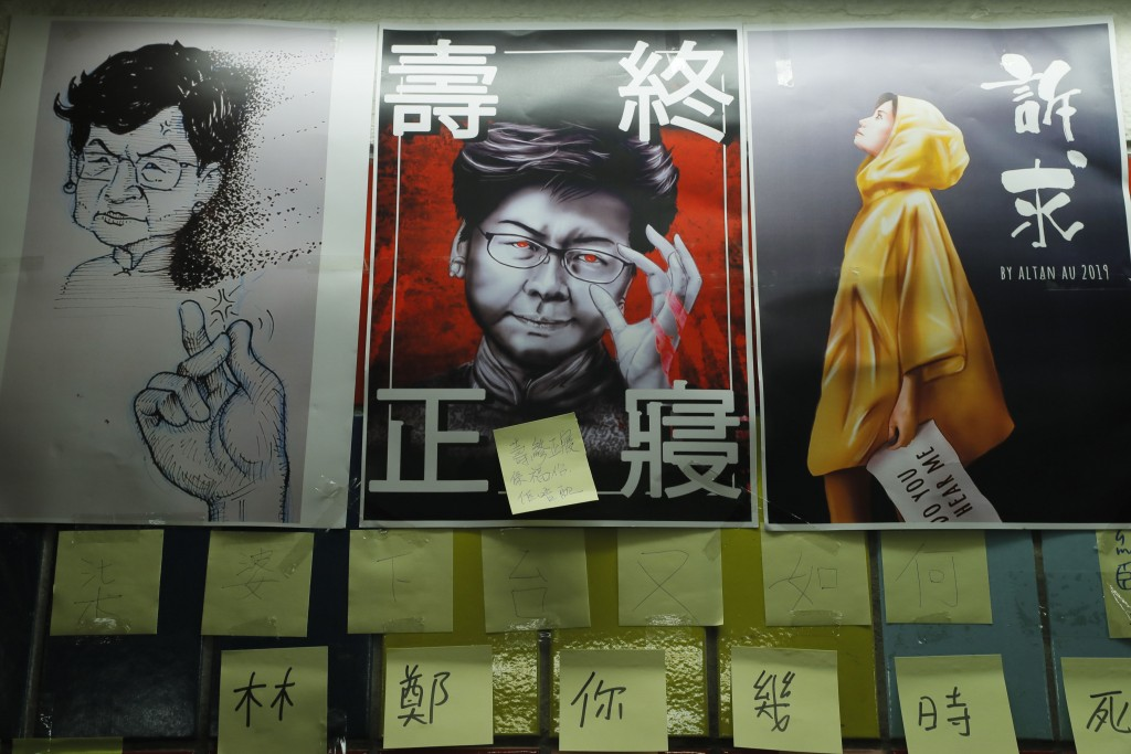 In this Friday, July 12, 2019, photo, post-it notes and a caricature of Hong Kong leader Carrie Lam are seen on their version Lennon Wall in Hong Kong