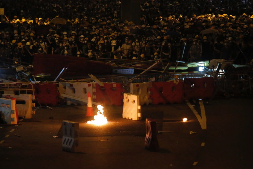 FILE - In this Wednesday, June 12, 2019, file photo, protesters gather behind barricade as a gasoline bomb thrown by a protester burns near the Legisl