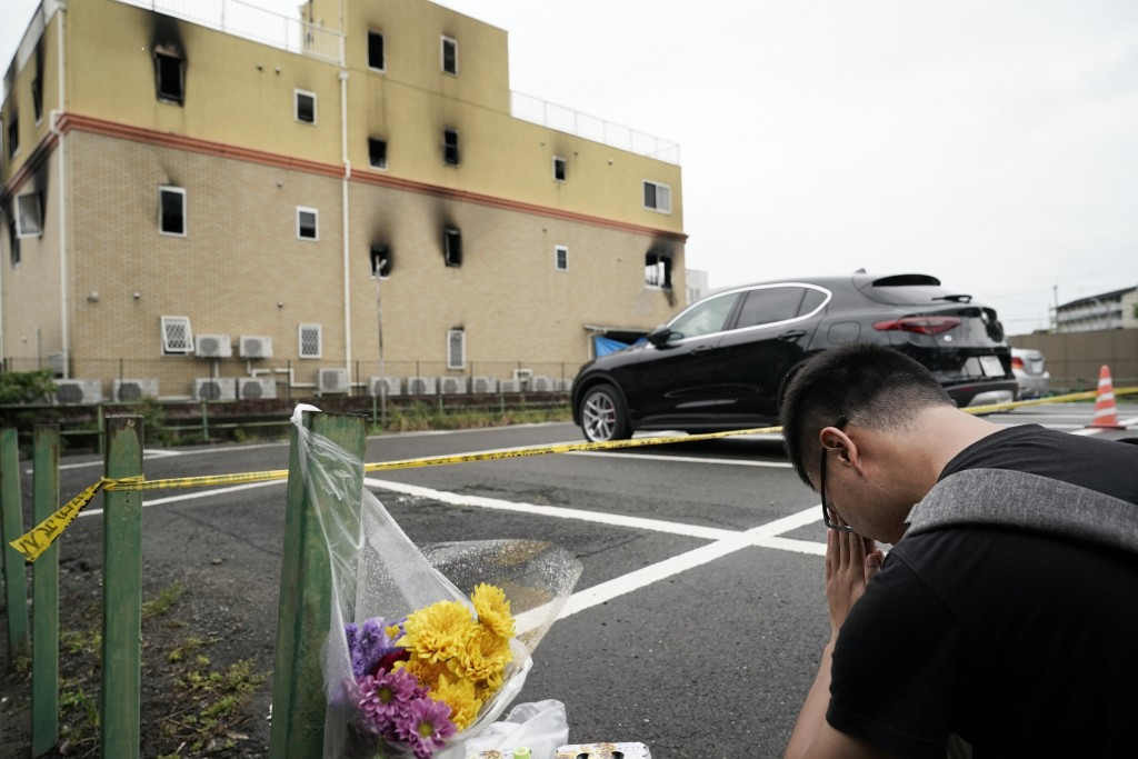 A man prays for the victims after placing flowers outside the Kyoto Animation Studio building consumed in an arson attack, Friday, July 19, 2019, in K...