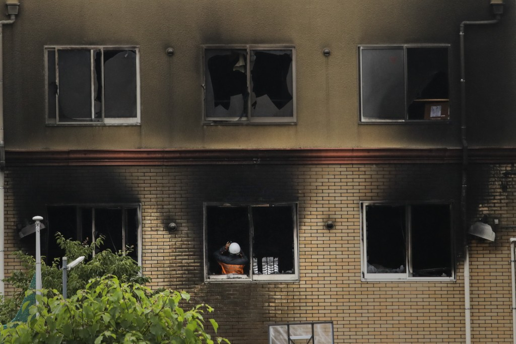 An investigator takes pictures inside the Kyoto Animation Studio building destroyed in an arson attack Friday, July 19, 2019, in Kyoto, Japan. A man s...