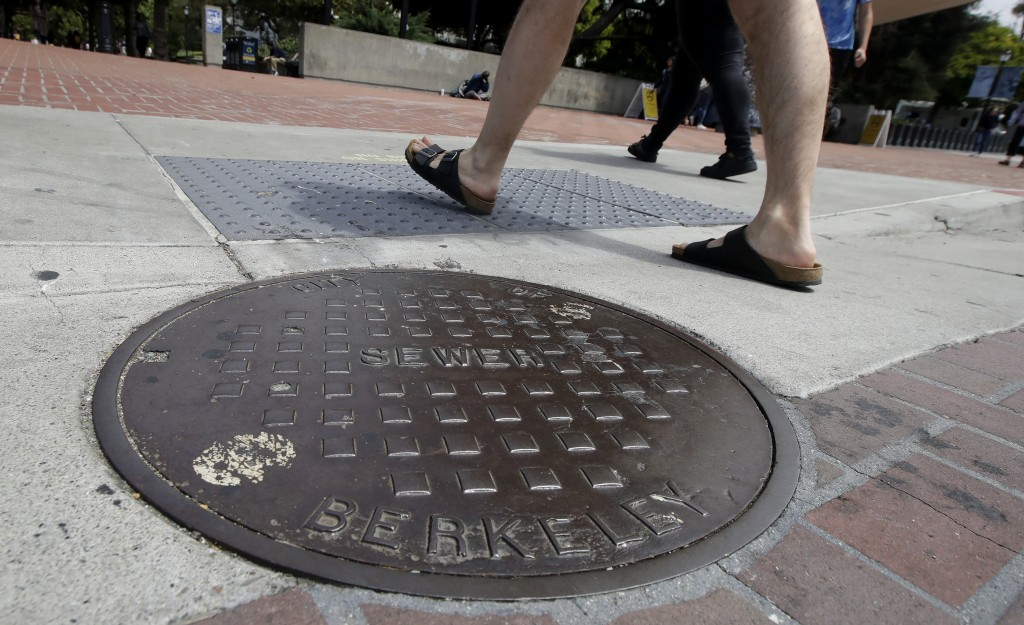Pedestrians walk past a manhole cover for a sewer in Berkeley, Calif., Thursday, July 18, 2019. Soon students in Berkeley, California will have to ple...