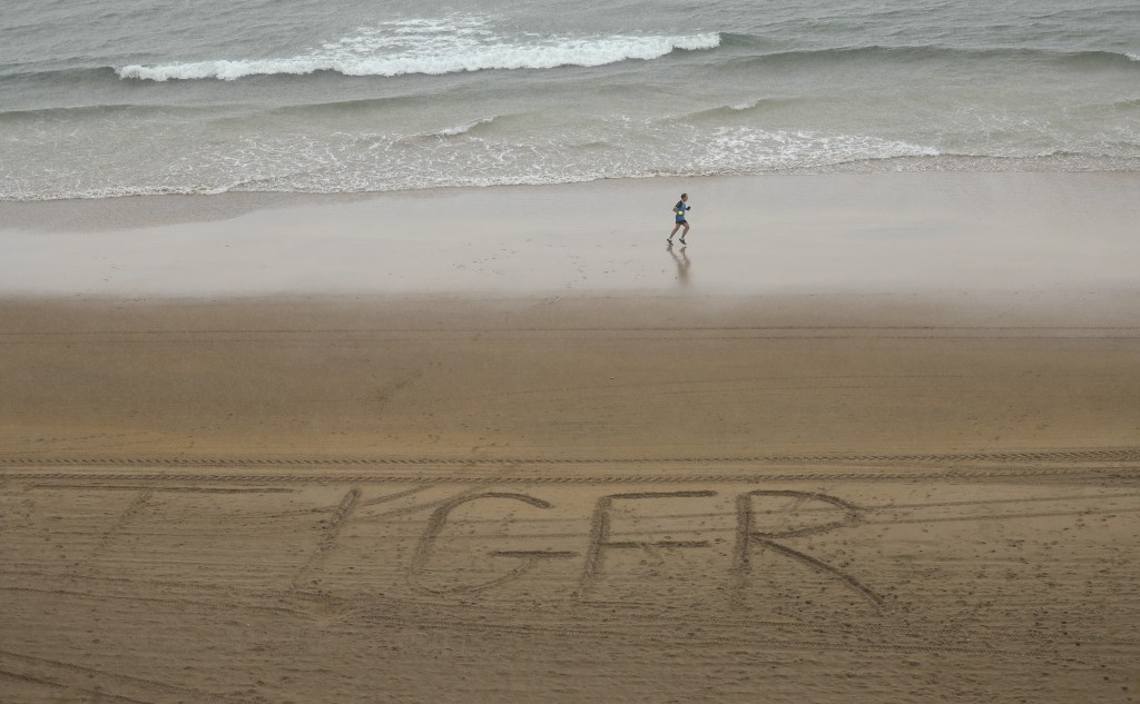 A runner jogs past 'Tiger' written in the sand on the beach below Portrush golf course as golfers compete in the first round of the British Open Golf ...