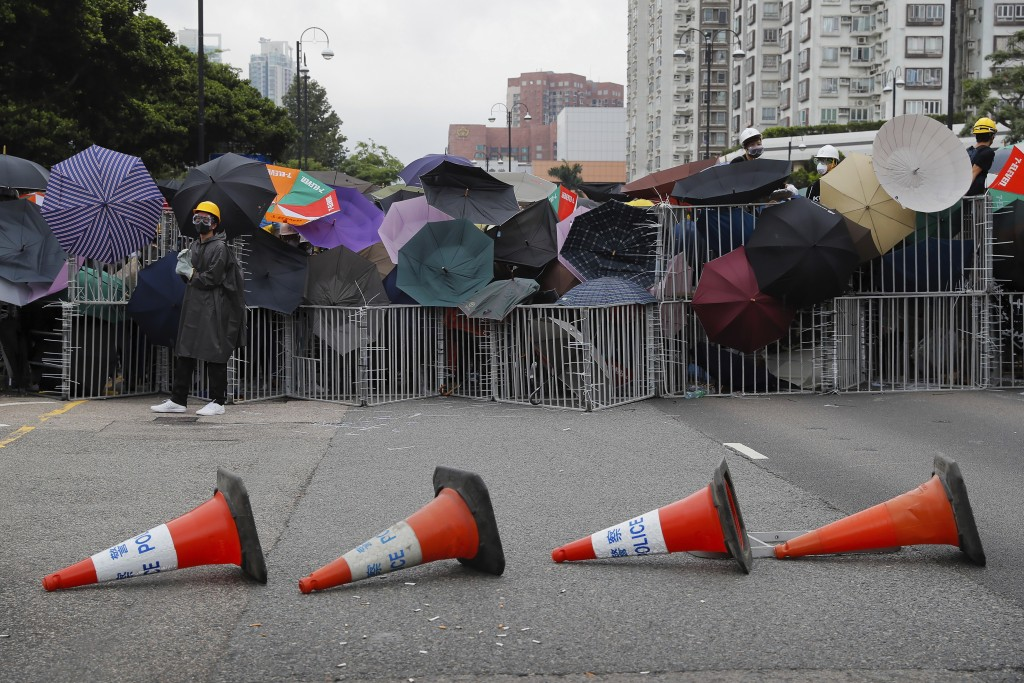FILE - In this Sunday, July 14, 2019, file photo, protesters use umbrellas and steel barricades to block a road during a march through Sha Tin Distric