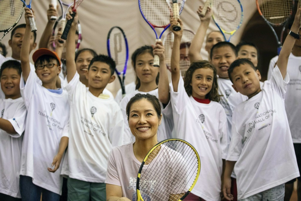 Two-time Grand Slam champion Li Na poses with students at the tennis clinic she led at the Sutton East Tennis Club Thursday, July 18, 2019, in New Yor...