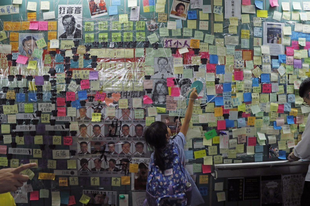 In this photo taken Friday, July 12, 2019, a child reaches out to post-it notes on the city's version of the Lennon Wall in Hong Kong. Hong Kong activ