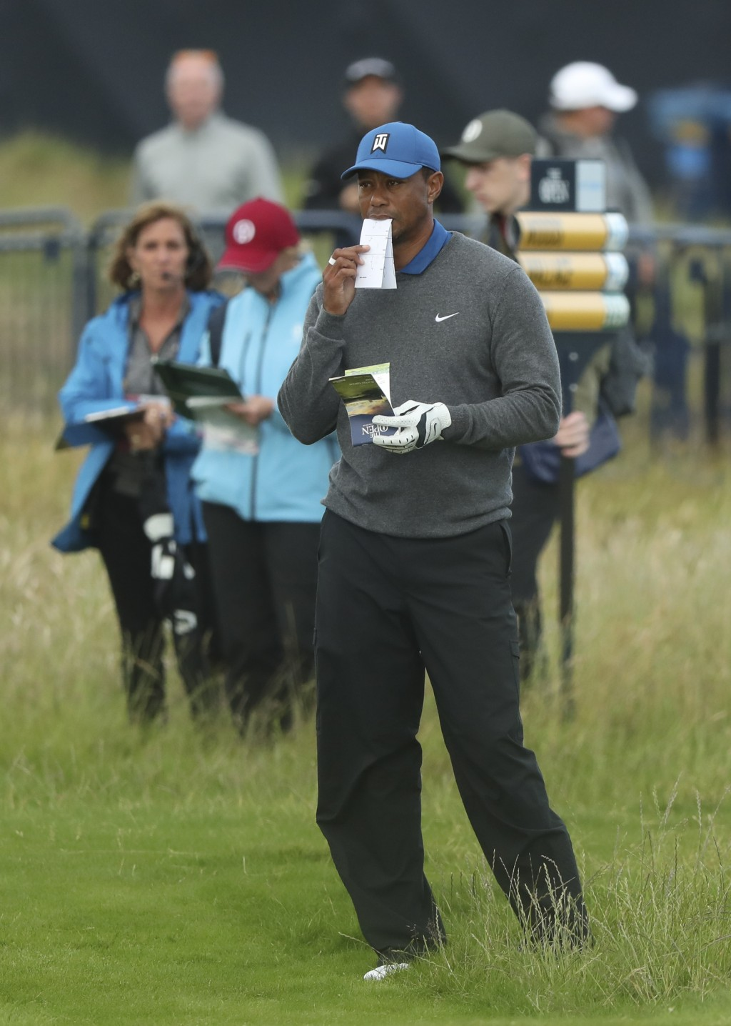 Tiger Woods of the United States looks at his playing guides on the 18th fairway during the first round of the British Open Golf Championships at Roya...