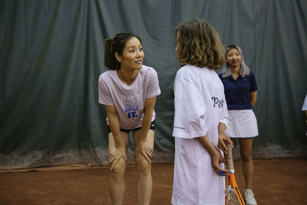 Two-time Grand Slam champion Li Na talks to one of the students during the clinic she led at the Sutton East Tennis Club Thursday, July 18, 2019, in N...