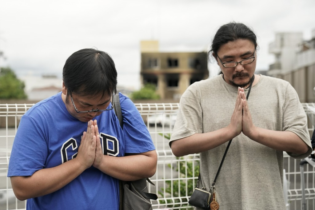 Two men pay respects at a makeshift memorial site to honor the victims of Thursday's fire at the Kyoto Animation Studio building, background center, F...