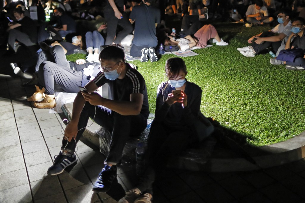 FILE - In this Wednesday, June 12, 2019, file photo, extradition law protesters browse their smartphones near the Legislative Council in Hong Kong. Th