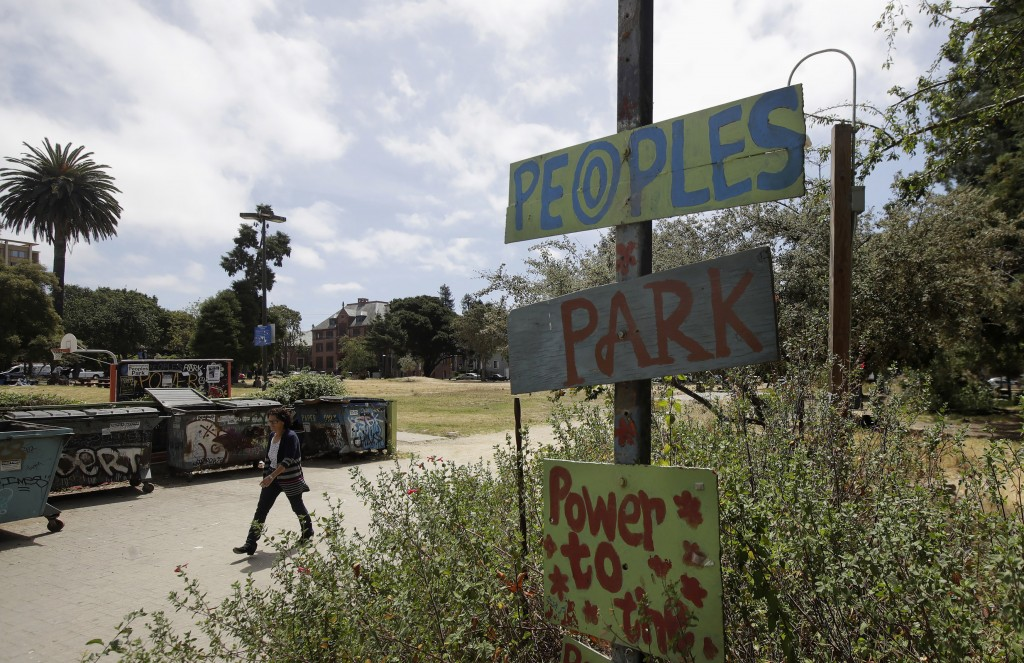 A woman walks behind a sign for People's Park in Berkeley, Calif., Thursday, July 18, 2019. Berkeley leaders voted unanimously this week to replace ab...