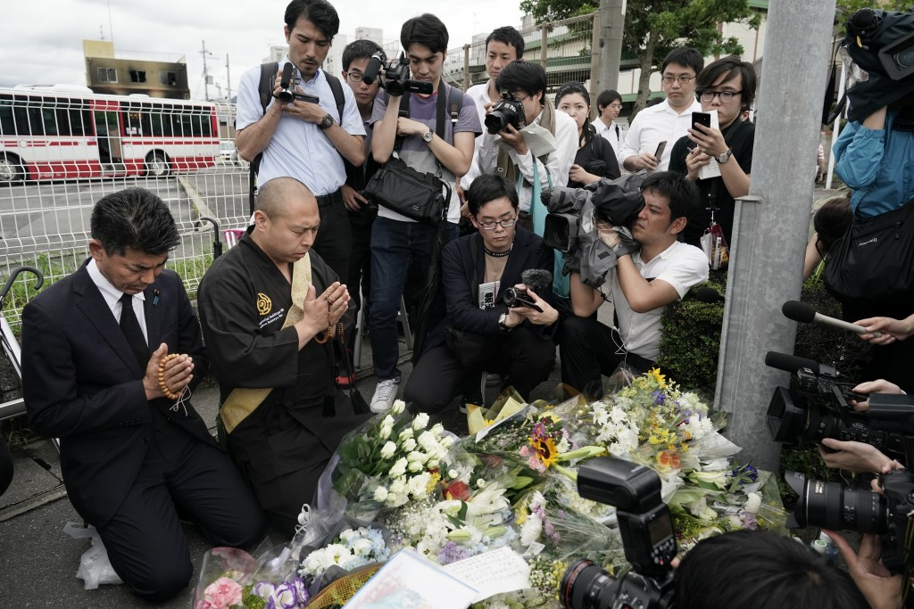 Japanese Diet member, Kenta Izumi, left, and Buddhist monk, Matsumoto Genkun, pay respects at a makeshift memorial site in front of burned Kyoto Anima...