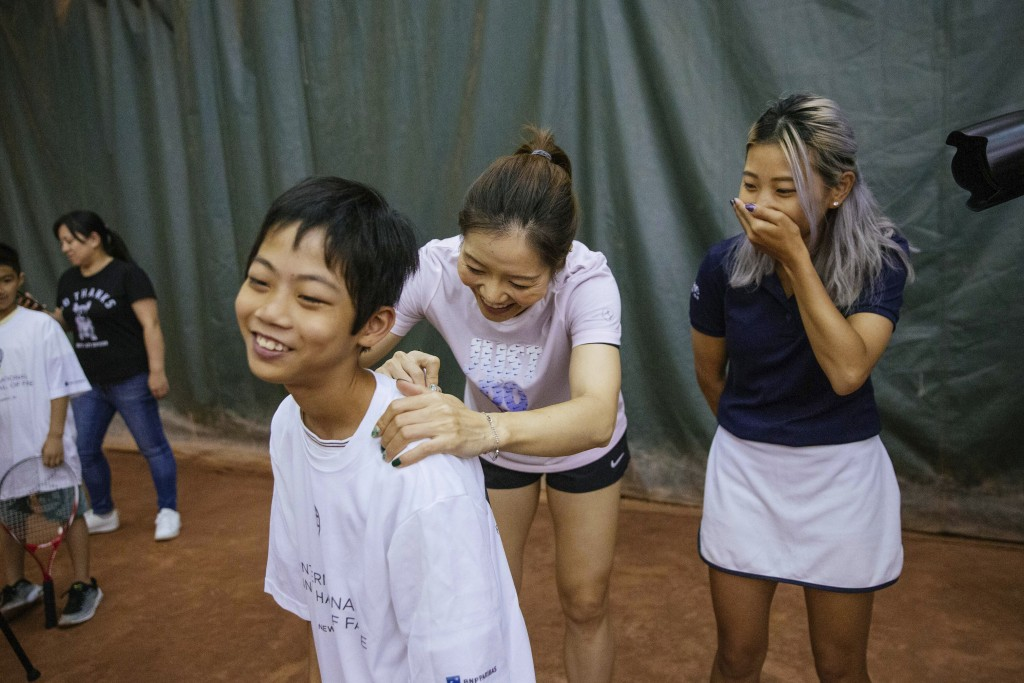 Two-time Grand Slam champion Li Na signs a tee-shirt for one of the students attending the clinic she led at the Sutton East Tennis Club Thursday, Jul...