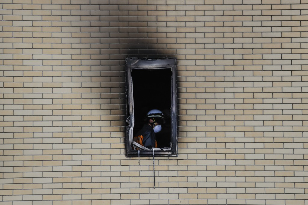 A firefighter is seen through the window of the Kyoto Animation Studio building consumed in an arson attack, Friday, July 19, 2019, in Kyoto, Japan. A...