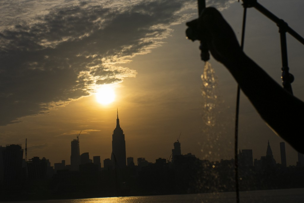 The sun rises over New York City and the Empire State Building while a man sprays water at Pier A on Saturday, July 20, 2019 in Hoboken, N.J. Temperat...