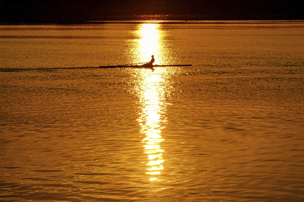 An early morning rower glides through the glare of the rising sun on the Potomac River at the start of a hot day in Washington, Saturday July 20, 2019...