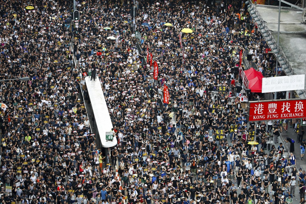 Protesters take part in a march on a street in Hong Kong, Sunday, July 21, 2019. Thousands of Hong Kong protesters marched from a public park to call