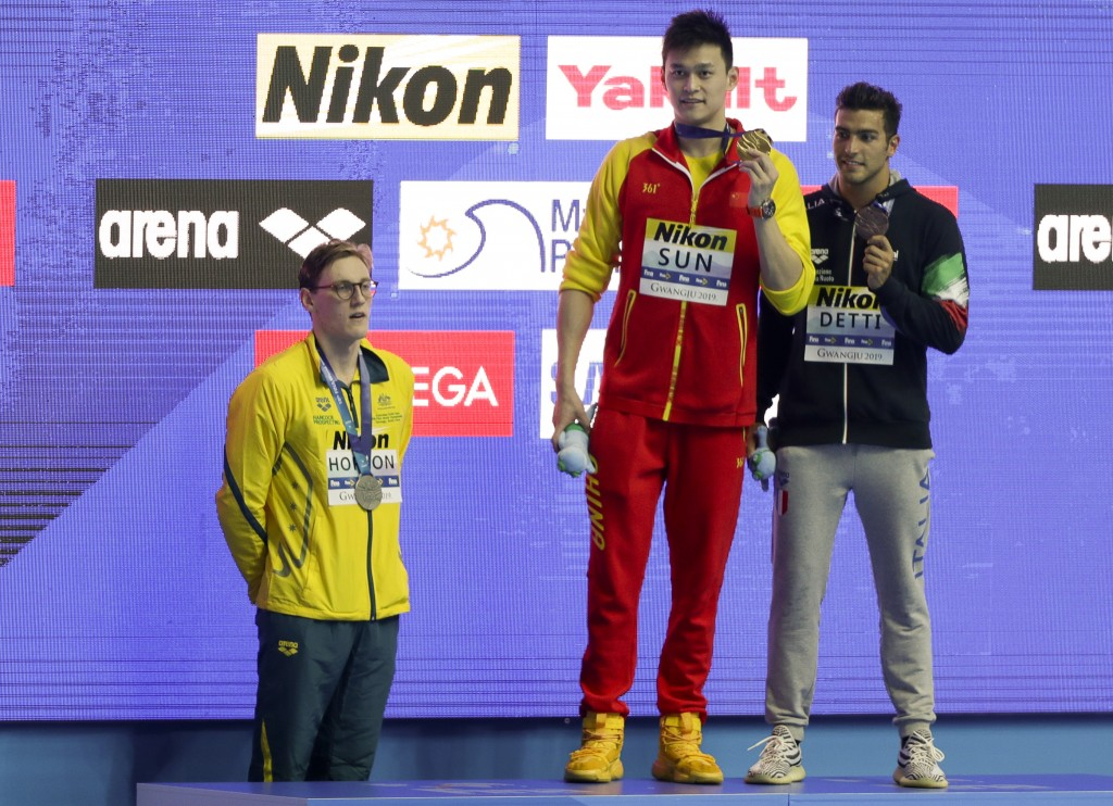 China's Sun Yang, centre, holds up his gold medal as silver medalist Australia's Mack Horton, left, stands away from the podium and bronze medalist It...
