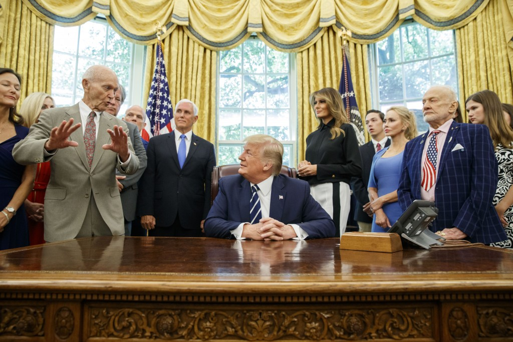FILE - In this Friday, July 19, 2019, file photo, President Donald Trump, center, listens to Apollo 11 astronaut Michael Collins, left, accompanied by...