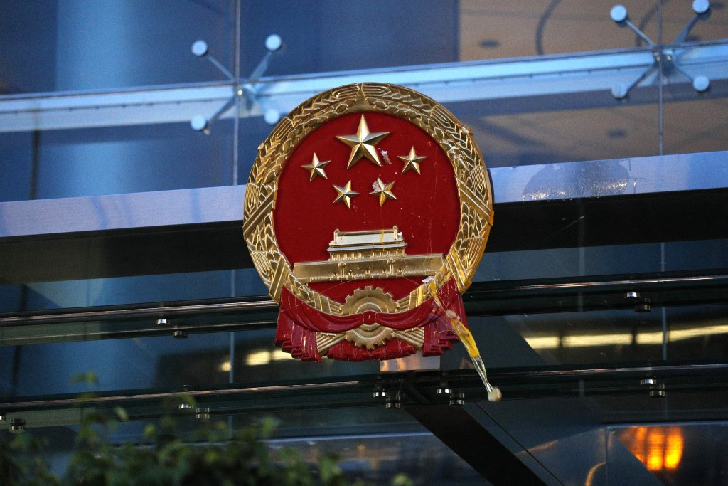 An egg thrown by a protester hits the National Emblem of the People's Republic of China at the Chinese Liaison Office in Hong Kong on Sunday, July 21,...