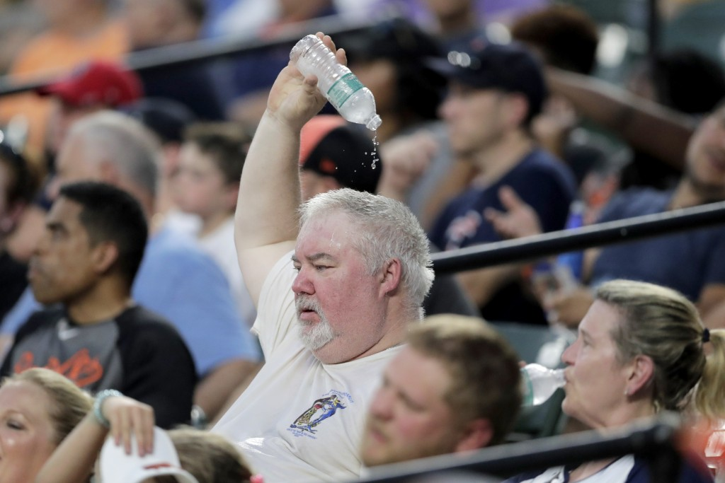 A spectator drops water on his head while watching the fourth inning of a baseball game between the Baltimore Orioles and the Boston Red Sox in hot we...