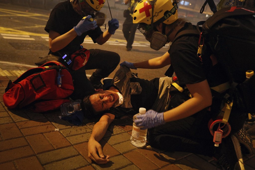 Medical workers help a protester in pain from tear gas fired by policemen on a street in Hong Kong, Sunday, July 21, 2019. Hong Kong police have throw...