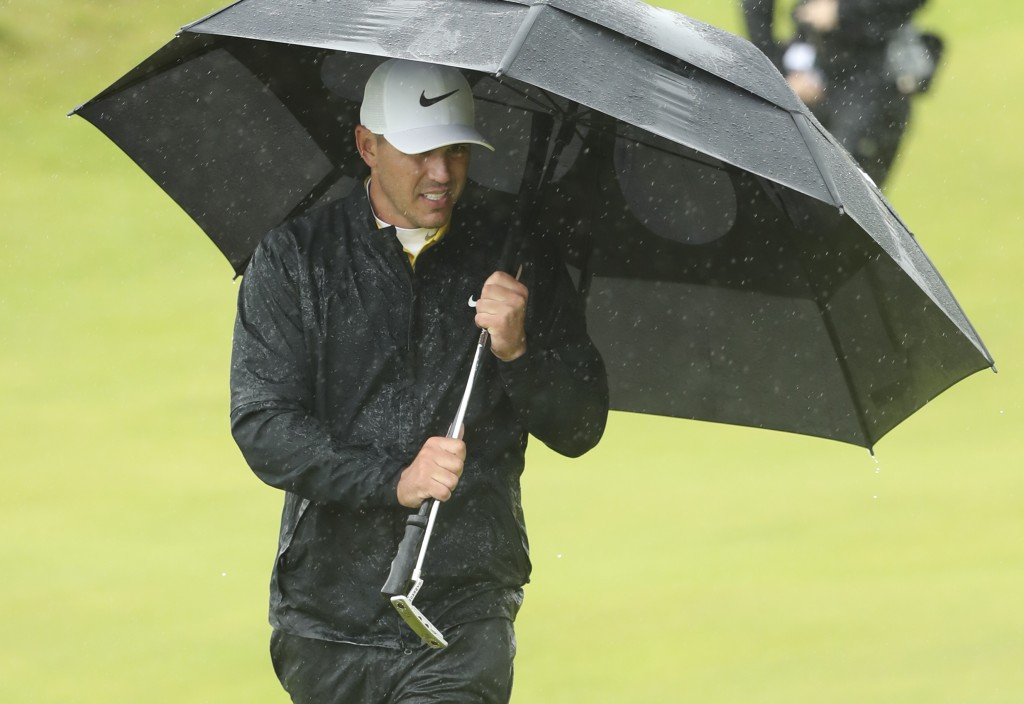 Brooks Koepka of the United States walks onto the 10th green as he shelters from the heavy rain under an umbrella during the final round of the Britis...