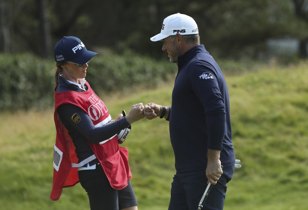 England's Lee Westwood touches fists with his caddie and girlfriend Helen Storey after getting a birdie on the 4th green during the third round of the...