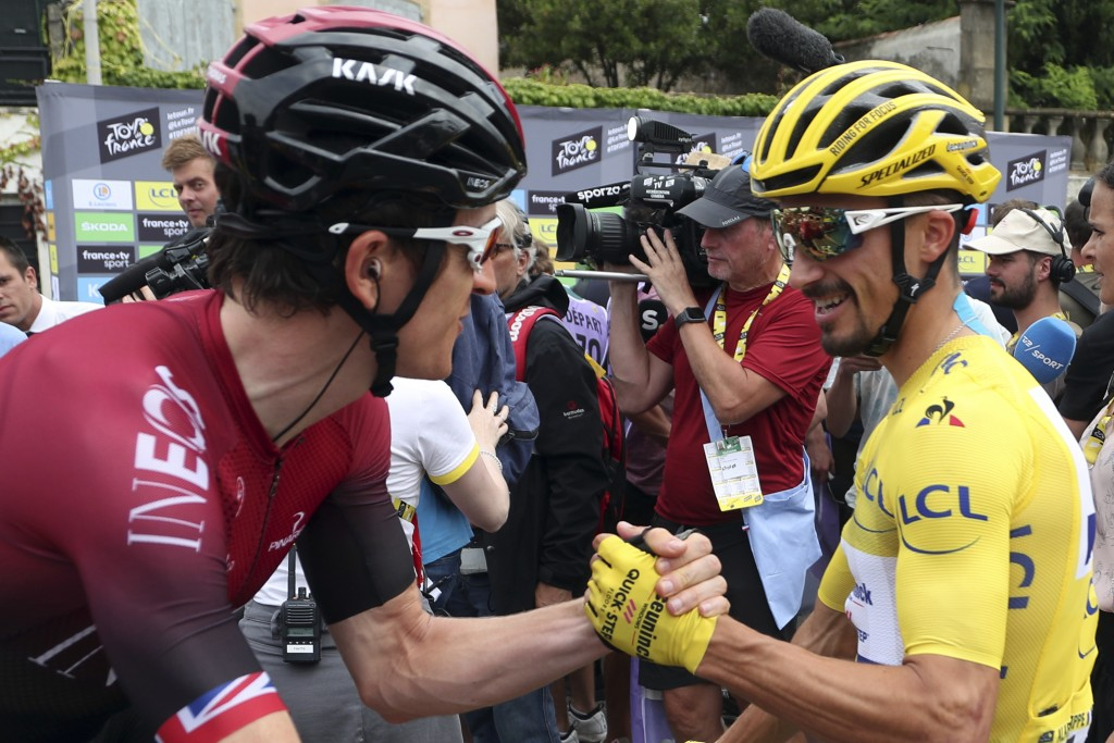 France's Julian Alaphilippe wearing the overall leader's yellow jersey shakes hands with Britain's Geraint Thomas as they arrive at the start of the f...