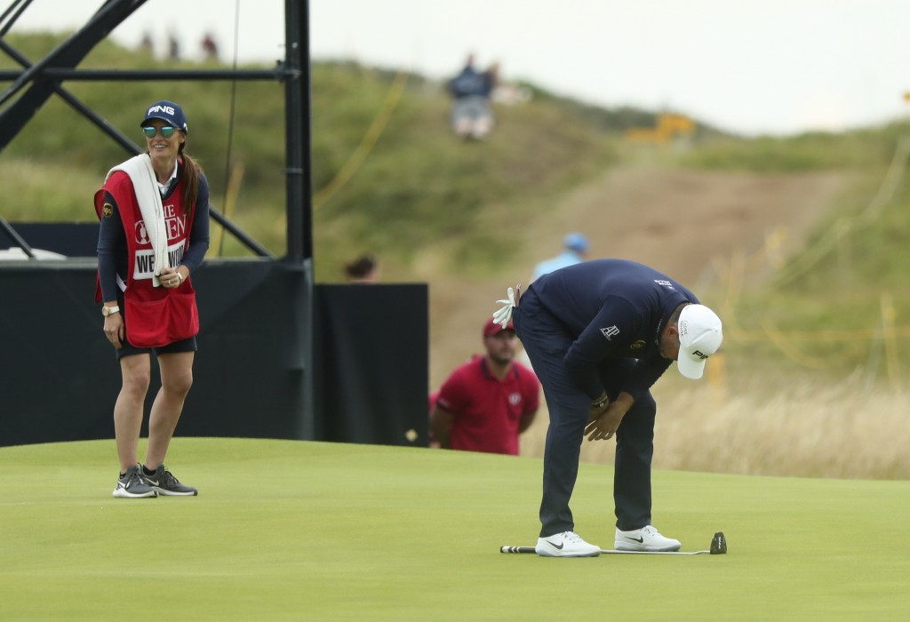 England's Lee Westwood looks down at his club after missing a shot on 14th green during the third round of the British Open Golf Championships at Roya...