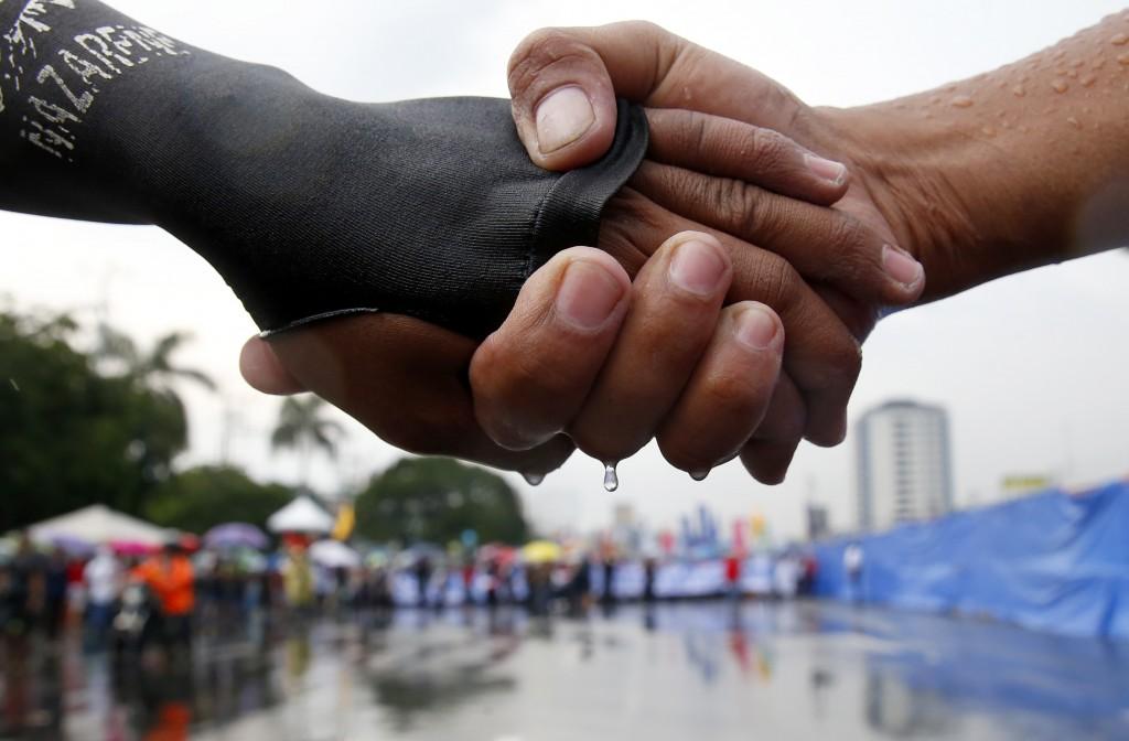 In this July 22, 2019, photo protesters link hands as they lead the march under the rain towards the Philippine Congress to protest the 4th State of t...