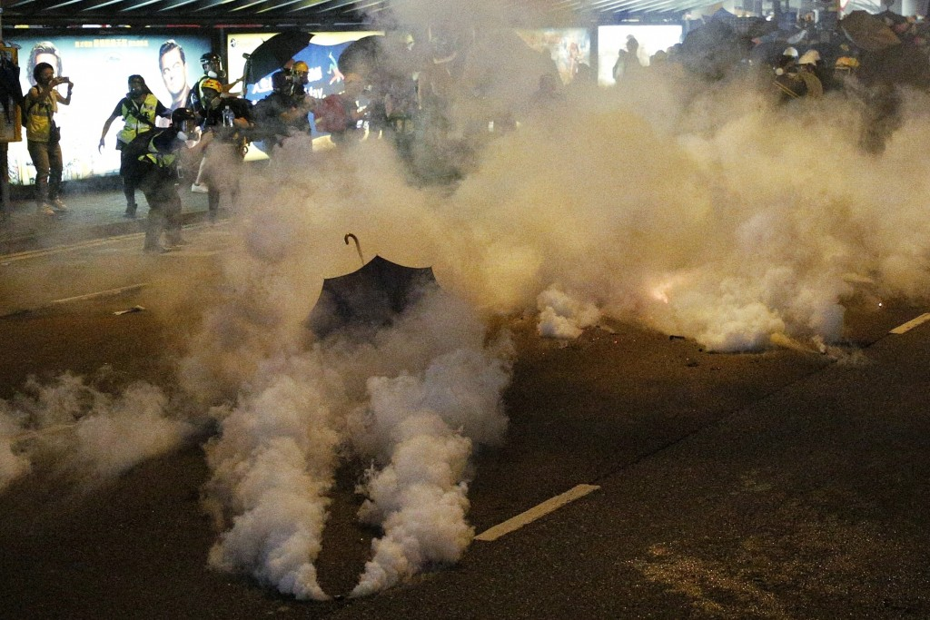 Protesters are engulfed by teargas during a confrontation with riot police in Hong Kong Sunday, July 21, 2019. Hong Kong police launched tear gas at p...