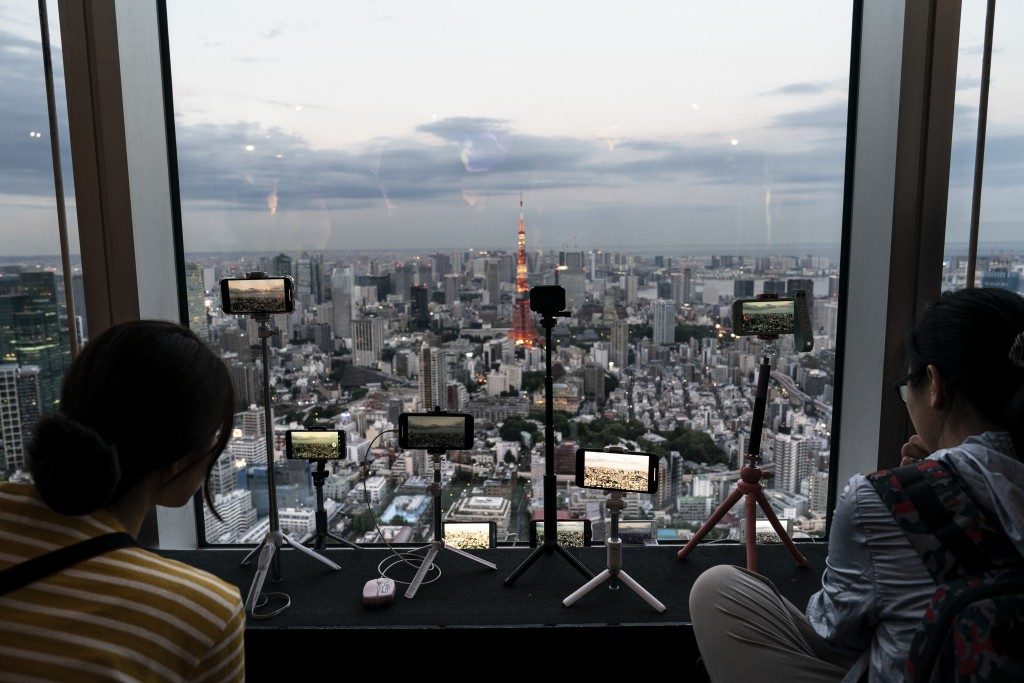 Smartphones are propped on tripods in the observation deck of the Mori Tower to capture Tokyo's skyline view in Tokyo, June 17, 2019. (AP Photo/Jae C....