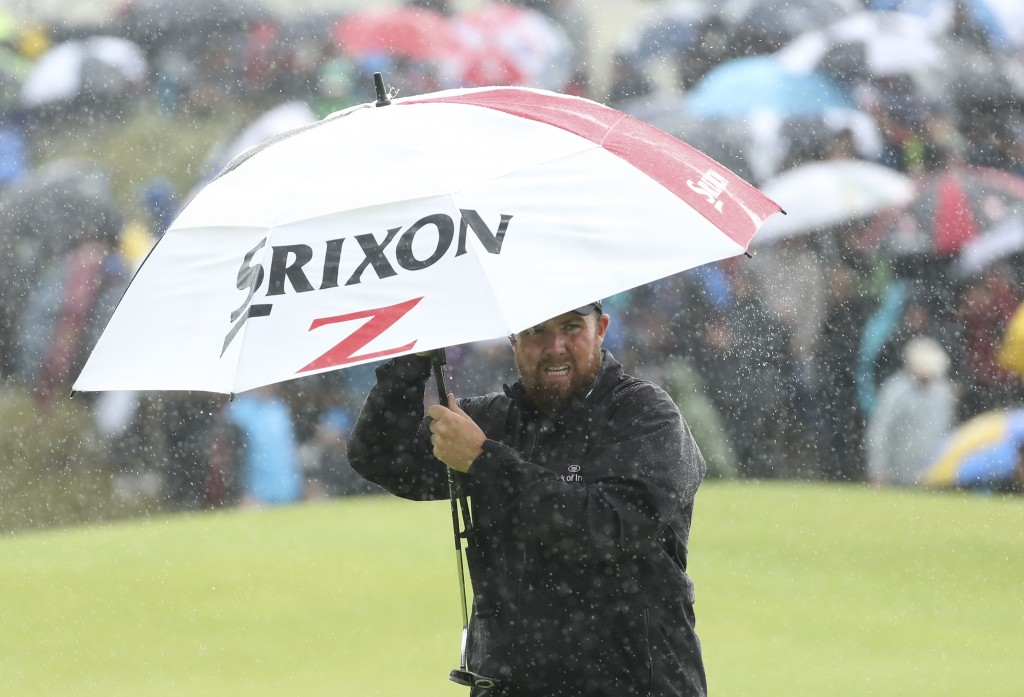 Ireland's Shane Lowry holds an umbrella in heaven rain on the 8th green during the final round of the British Open Golf Championships at Royal Portrus...