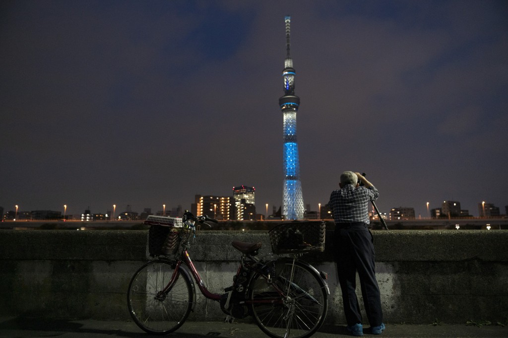 Kiyoshi Ozawa, 77, takes pictures of the Skytree, the world's tallest tower in Tokyo, June 20, 2019. (AP Photo/Jae C. Hong)