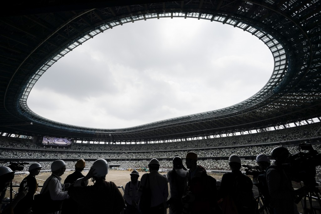 FILE - In this July 3, 2019, file photo, media tour the New National Stadium in Tokyo. Scandals and rising costs have not deterred interest in Japan i...