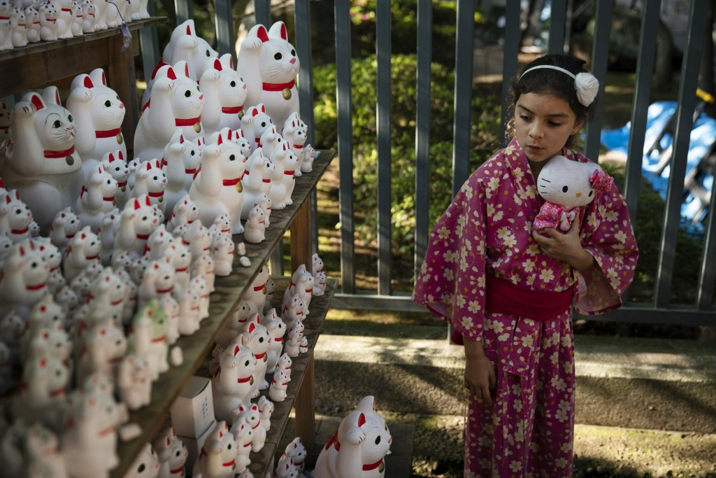 Holding a Hello Kitty doll, 8-year-old Grace Fetherston, of Australia, looks at beckoning lucky cat figurines at Gotokuji Temple in Tokyo, June 25, 20...