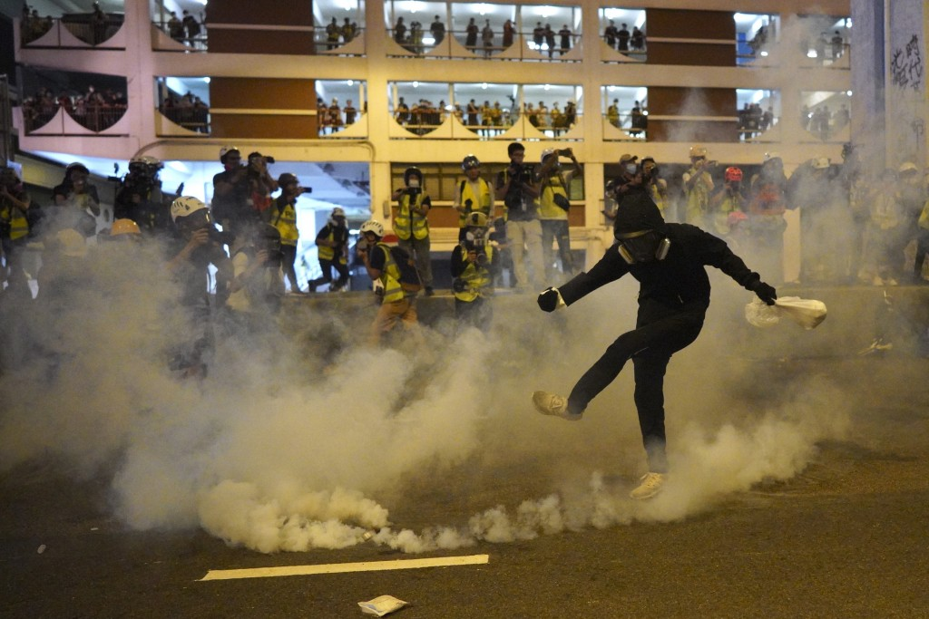 A protestor kicks a tear gas canister during confrontation in Hong Kong Sunday, July 21, 2019. Hong Kong police launched tear gas at protesters Sunday