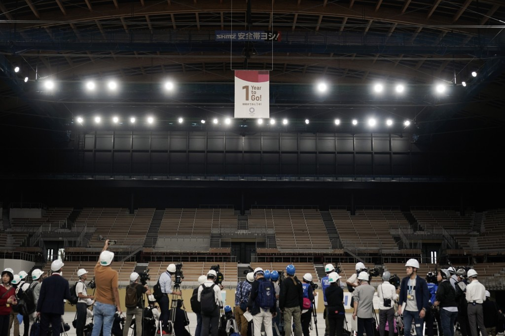 "Members of the media gather near a ""1-Year to Go"" banner during a tour Monday, July 22, 2019, in Tokyo. Despite scandals, rising costs and doubts abou..."