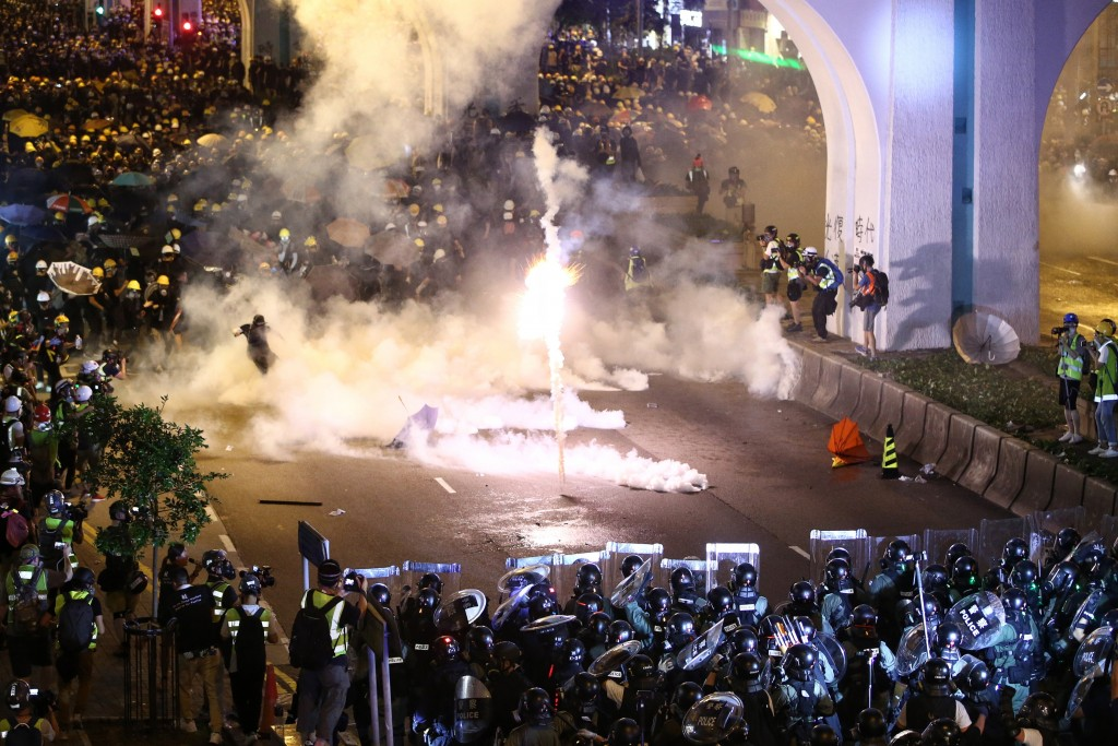 Protesters are engulfed by teargas during a confrontation with riot police in Hong Kong Sunday, July 21, 2019. Hong Kong police launched tear gas at p