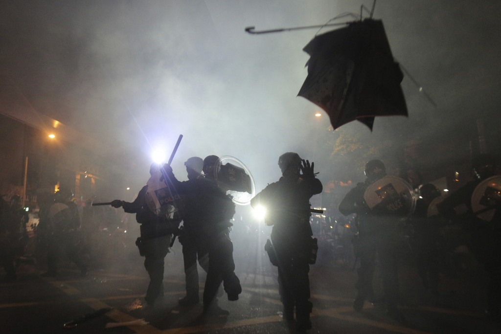 A broken umbrella flies by near riot police, during confrontation with protesters in Hong Kong Sunday, July 21, 2019. Hong Kong police launched tear g...