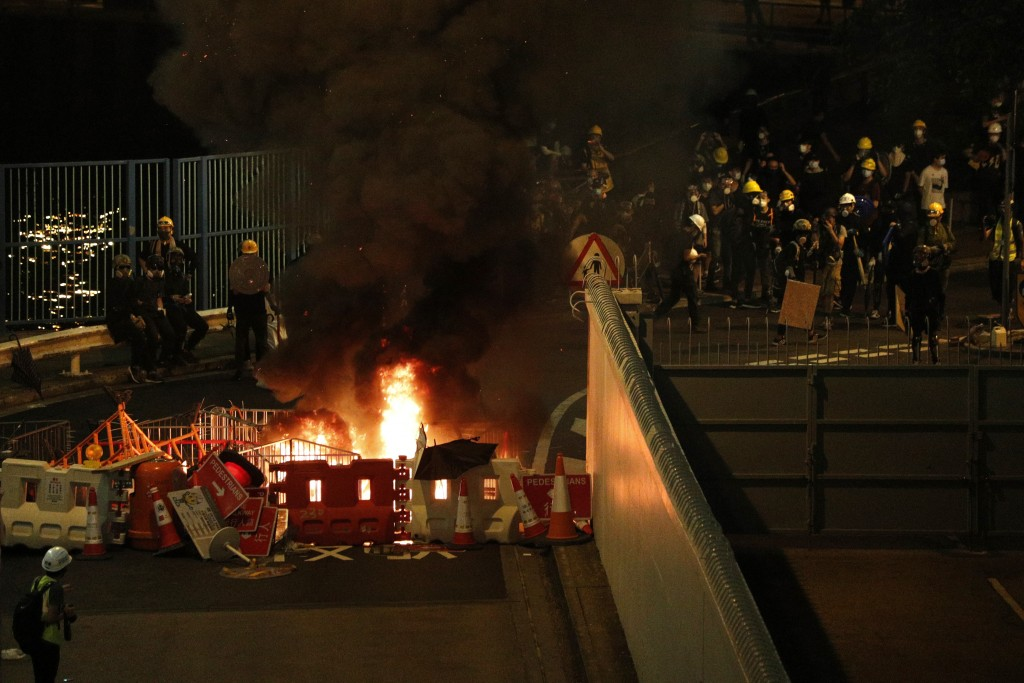 Protesters set fire to a barricade to prevent riot police officers from advancing in Hong Kong on Sunday, July 21, 2019. Hong Kong police launched tea