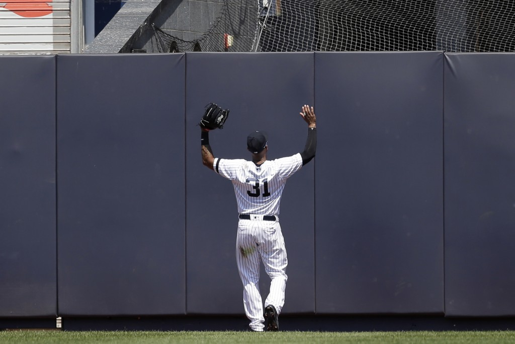 New York Yankees center fielder Aaron Hicks reacts as Colorado Rockies' Trevor Story hits a two-run double during the fourth inning of a baseball game...