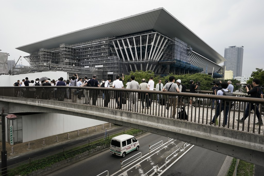 FILE - In this July 3, 2019, file photo, members of the media gather outside the Tokyo Aquatics Center, a venue for swimming and diving at the Tokyo 2...