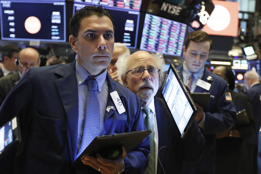 FILE - In this Thursday, July 18, 2019, file photo traders Craig Spector, left, and Peter Tuchman, center, work on the floor of the New York Stock Exc...
