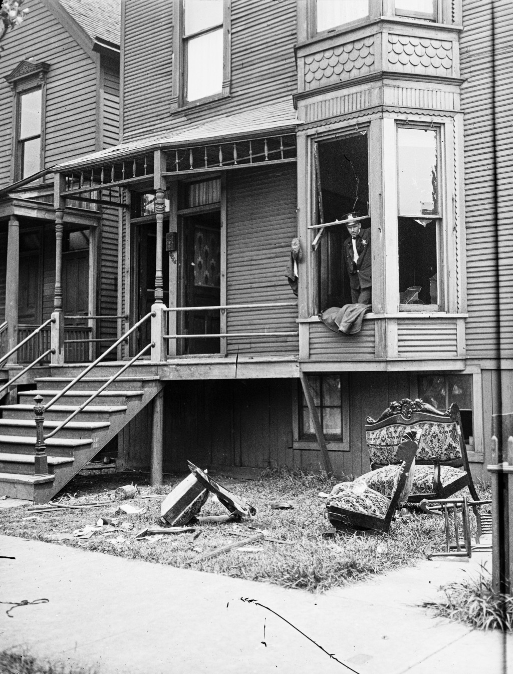 In this 1919 photo provided by the Chicago History Museum, police look through a broken window of a house during the race riots in Chicago. Broken fur...