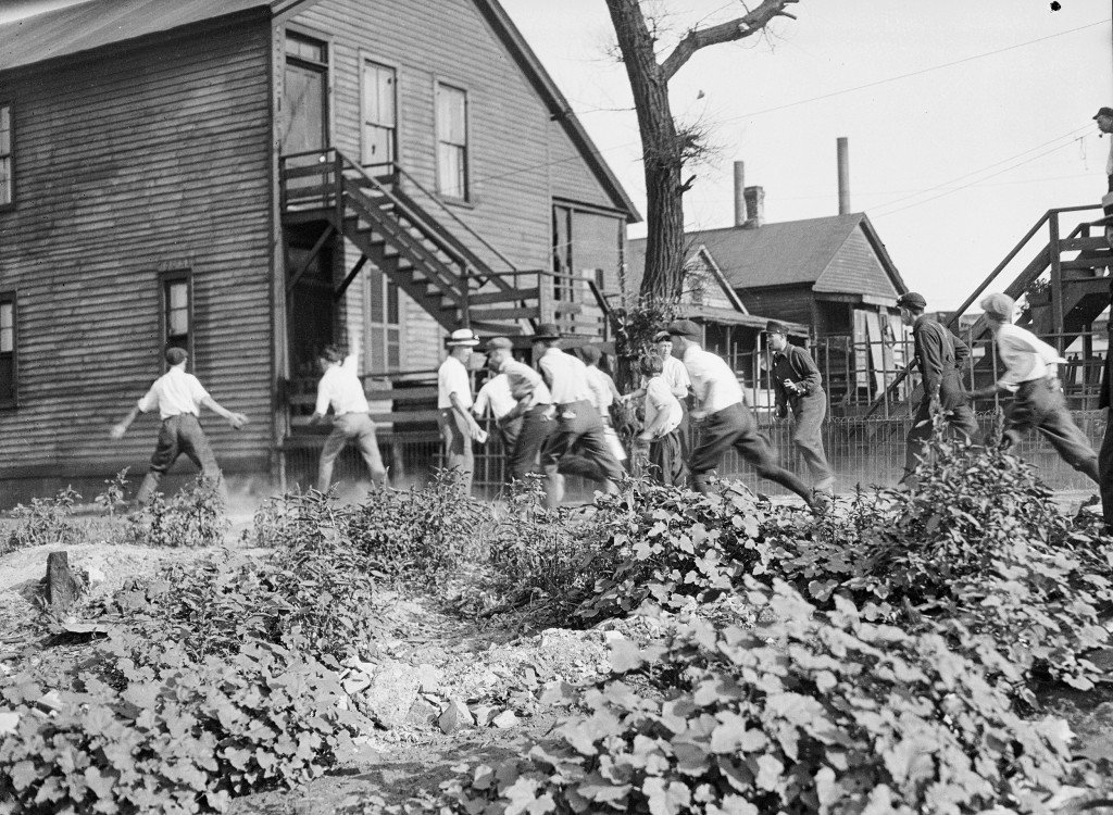 In this 1919 photo provided by the Chicago History Museum, a victim is stoned and bludgeoned under a corner of a house during the race riots in Chicag...
