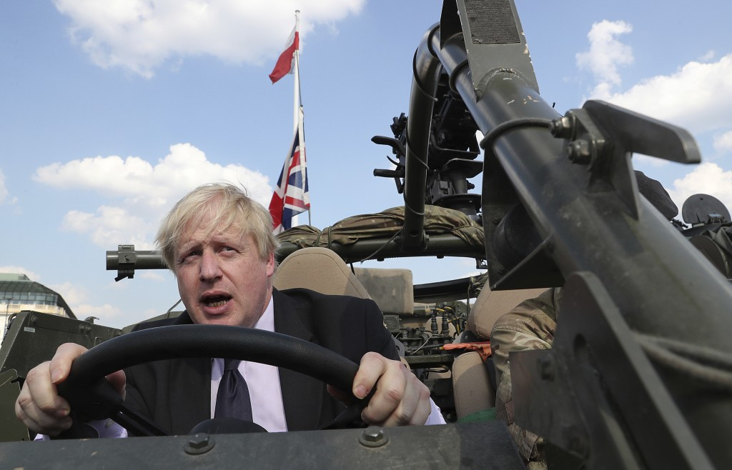 FILE - In this Thursday, June 21, 2018 file photo Britain's Foreign Secretary Boris Johnson talks to a British armed forces serviceman based in Orzysz...