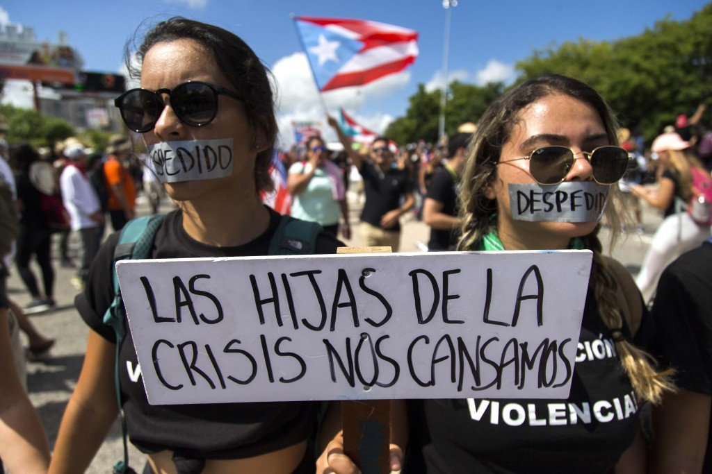 """Demonstrators with their mouths covered with a tape and a sign that reads in Spanish """"The daughters of the crisis got tired"""" during a march on Las Ame..."""
