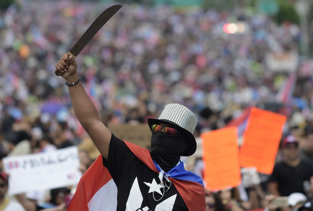 A demonstrator brandishes a machete during a march on Las Americas highway to demand the resignation of governor Ricardo Rossello, in San Juan, Puerto...