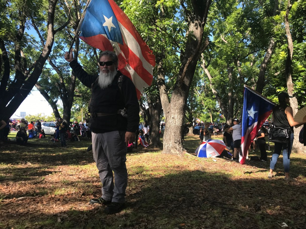 German Alejandro Ortiz, a 43-year-old businessman holds a Puerto Rico flag as he poses for a photo during a protest to demand the resignation of Gover...